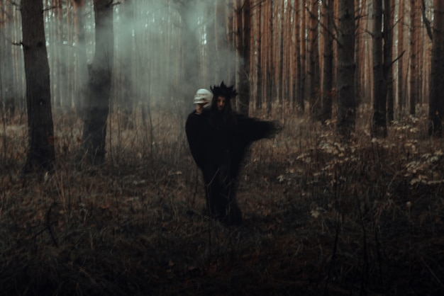 Blurry silhouette of an evil black witch with a skull in her hands performing an occult satanic ritual in a dark gloomy forest