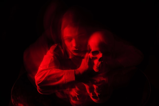 Blurry terrible portrait of a ghost witch girl with a dead man's skull in her hands