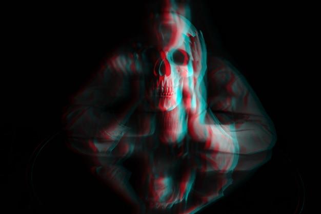 어두운 배경에서 손에 죽은 남자의 두개골이 있는 유령 마녀 소녀의 흐릿한 끔찍한 초상화. 3d 글리치 가상 현실 효과가 있는 흑백