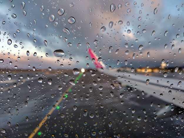 Blurry view of an airport runway through an airplane window with rain drops