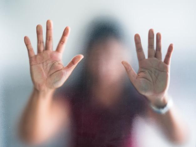Размытые руки женщины за матовым стеклом метафора паника и негатив темные эмоциональные