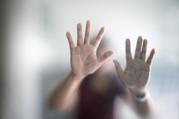 Blurry woman hand behind frosted glass metaphor panic and negative dark emotional