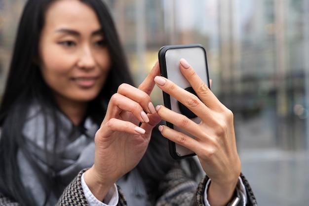 Blurry woman taking selfie in city