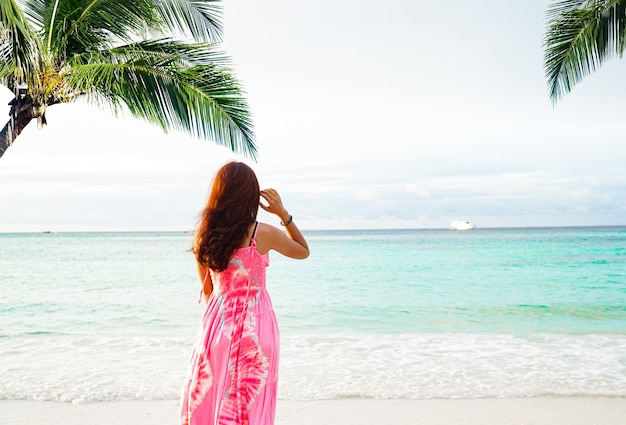 Blurry women wearing a pink dress  standing alone on the beach under coconut tree