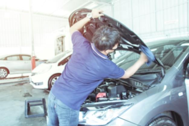 ぼやけた労働者の男は、車のボンネットとエンジンルームを掃除して車のボンネットを開けます。