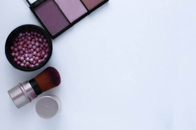 Шарики румян розово-кремового цвета бронзером и кисточкой для нанесения румян на белый фон с ...