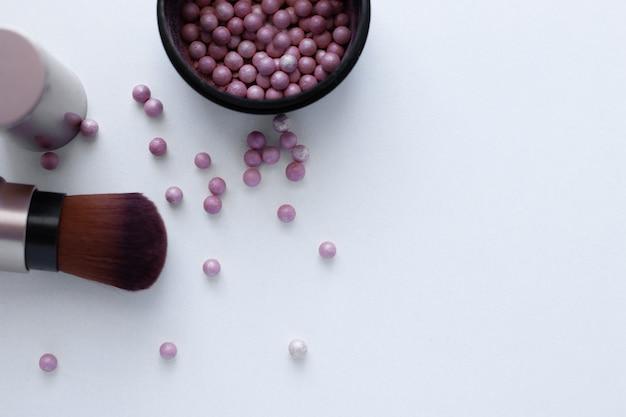 Шарики румян розово-кремового цвета и кисть для нанесения румян на белом фоне с пла ...