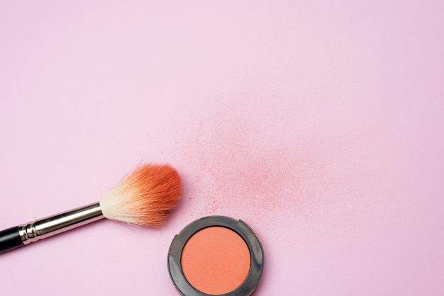 The blush brush lies on a pink background next to the orange pressed blush. powder texture on background