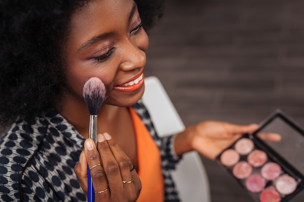 Blush palette. smiling dark-skinned woman with curly hair feeling gorgeous while sitting in front of the mirror