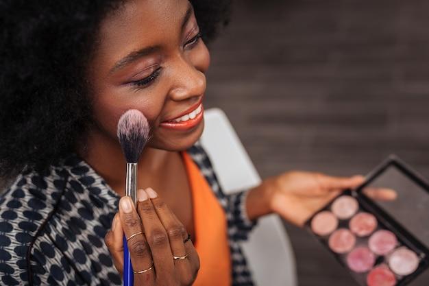 ブラッシュ パレット。鏡の前に座ってゴージャスな感じの巻き毛を持つ笑顔の浅黒い肌の女性