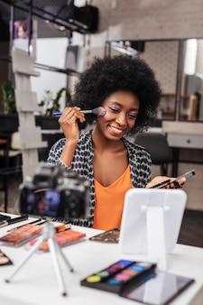블러셔 팔레트. 화장을하는 동안 거울 앞에 앉아 곱슬 머리를 가진 긍정적 인 어두운 피부의 여성