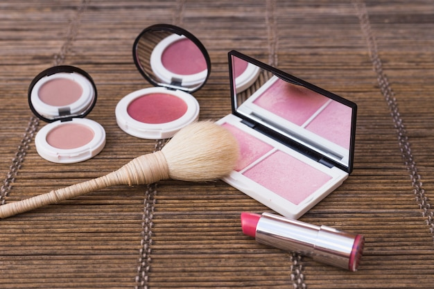 Blusher palettes and pink lipstick with makeup brush on placemat