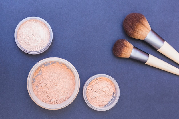 Blusher powder and two makeup brush on blue backdrop