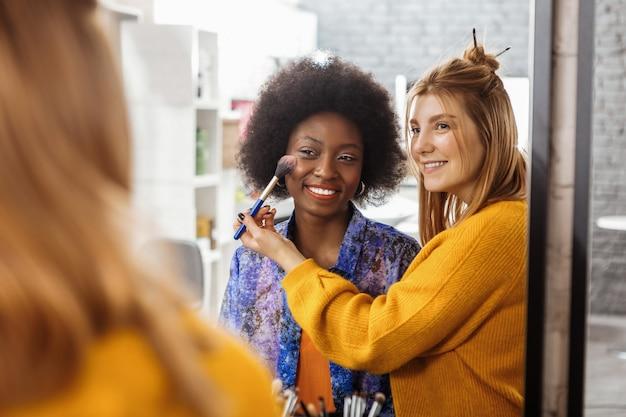 Образец румян. светловолосый улыбающийся стилист в желтом свитере примеряет новый образец румян на темнокожую модель