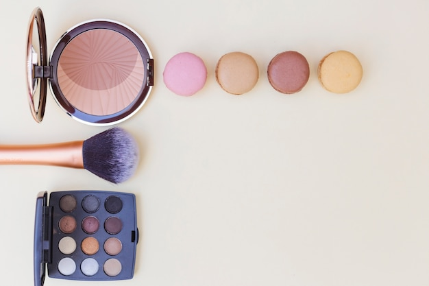 Blusher with macaroon; makeup brush and eyeshadow palette on beige background