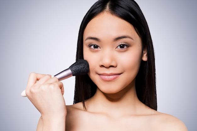 얼굴이 붉어지는 아름다움. 아름 다운 젊고 벗은 아시아 여자 뺨에 화장 브러시를 들고 회색 배경에 서있는 동안 미소