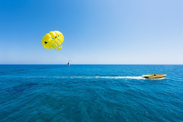 Bluw sea in protaras, cyprus island with yellow parasailing and a boat