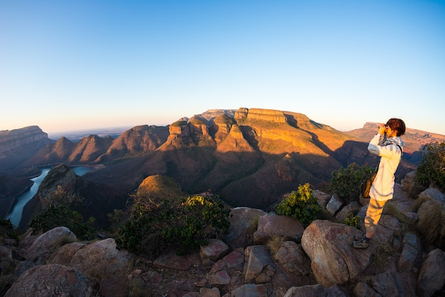 Blyde river canyon, famous travel destination in south africa. tourist looking at panorama with binocular. last sunlight on the mountain ridges.