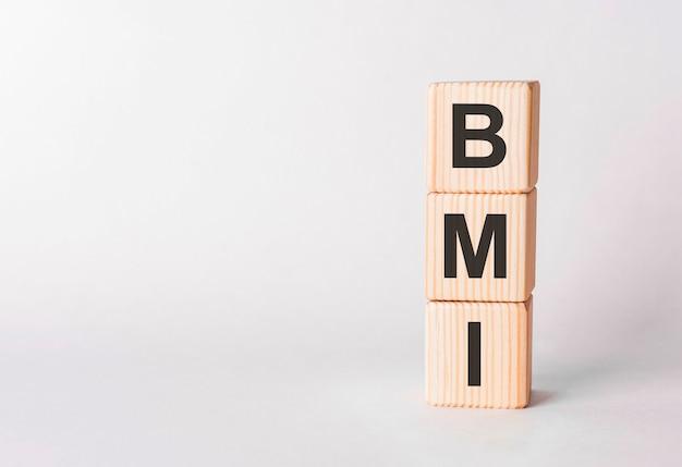 白い背景、コピースペースに柱の形で木製ブロックのbmi文字