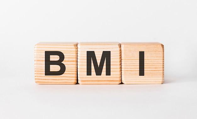 白い背景の上の柱の形で木製ブロックのbmi文字