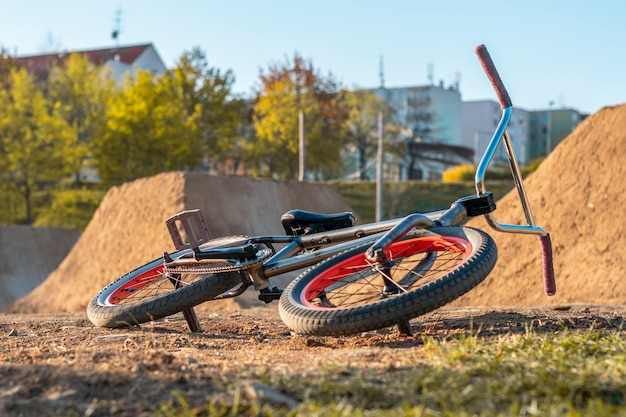 Bmx bike on the track with jumps on the background with houses