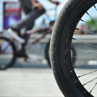 A bmx bike wheel against the backdrop of a blurred street with cycling riders. extreme sports concept