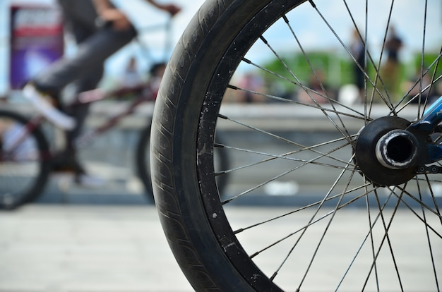 A bmx bike wheel against the backdrop of a blurred street with cycling riders.