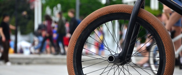 A bmx bike wheel against the backdrop of a blurred street