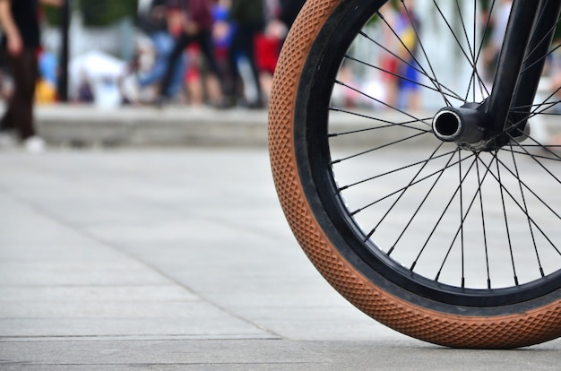 A bmx bike wheel against a blurred street with cycling riders. extreme sports concept