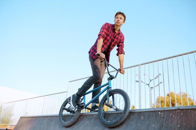 Байкер bmx делает трюк, подросток на тренировке в скейтпарке. экстремальный велосипедный спорт, опасные велотренировки, риск-стрит, езда на велосипеде в летнем парке