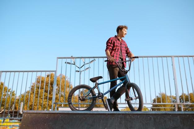 Байкер bmx делает трюк, подросток на тренировке в скейтпарке. экстремальный велосипедный спорт, опасные велотренировки, риск-стрит, езда на велосипеде в летнем парке Premium Фотографии