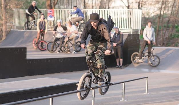 Молодой человек выполняет трюк на bmx в скейт-парк на фоне людей с велосипедами. турнир bmx. bmx concept
