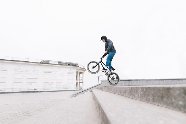 Молодой человек прыгает на велосипеде bmx вдоль лестницы. bmx фристайл на городской пейзаж. концепция bmx.