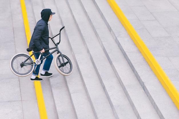 Bmxで自転車で街を歩きます。 bmxのコンセプト。男は二階に行きます。上面図。 copyspace。