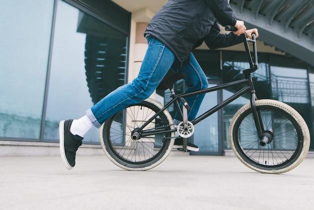 Человек ехал на велосипеде bmx в городе на архитектуре. кататься на велосипеде. bmx культура