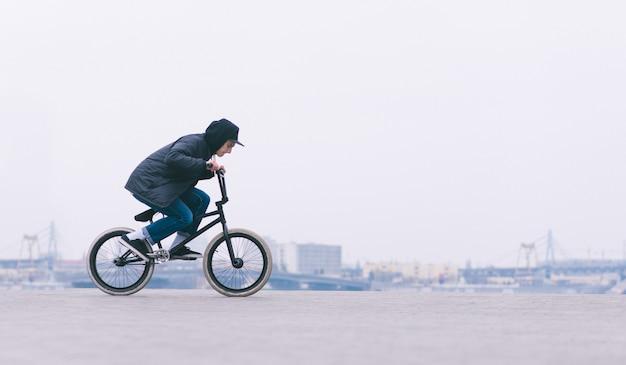 Молодой bmx райдер на велосипеде по минималистскому городу. велосипедист bmx собирается сделать трюк.