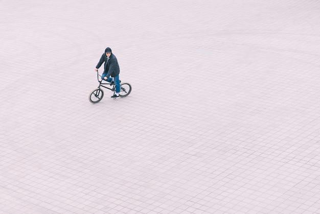 Мужчина едет на квадрате на велосипеде bmx, вид сверху. концепция bmx