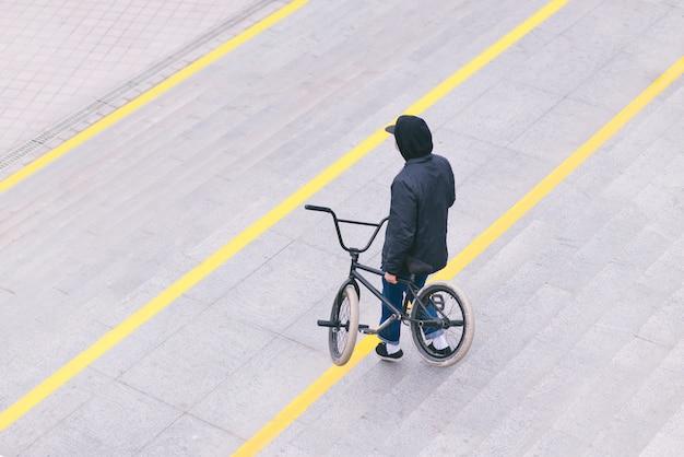 街を歩くスタイリッシュなbmxバイク少年。 bmxのコンセプト。上面図