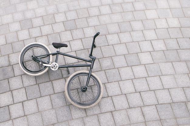 Велосипед bmx лежит на земле, вид сверху. copyspace.