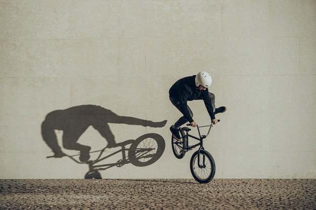 Bmx flatland rider doing a spin with his shadow projected in a stone wall