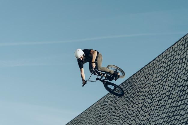 Bmxの男性ライダーが石レンガの自転車公園で彼の自転車で下って行きます。