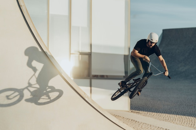 Bmx male rider jumping with his shadow projected on a white wall.