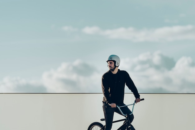 Bmx male rider looking away with white fence and cloudy sky in background