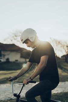 Bmx male rider looking down with sunset in background