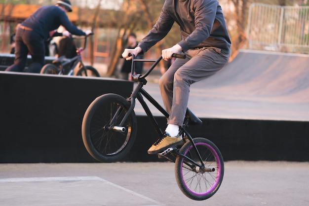 Bmx rider делает трюки на bmx в скейтборде. вечерняя тренировка на bmx. велосипедист едет на заднем колесе. концепция bmx
