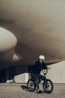 Bmx rider looking away sitting in his bike with modern building in background