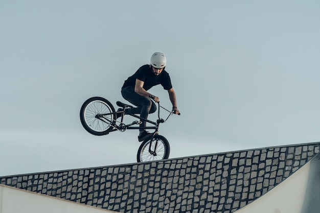 Bmx rider making a reversed wheelie on top of stone bricks bike park