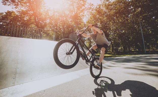 Bmx rider performing tricks at skatepark.
