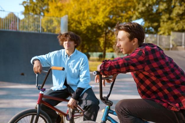 Велосипедисты bmx, тренируются на рампе в скейтпарке. экстремальный велосипедный спорт, опасные велотренажеры, уличная езда, подростки на велосипеде в летнем парке