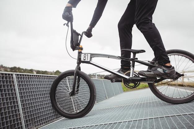Велосипедист готовится к гонкам bmx на стартовой рампе